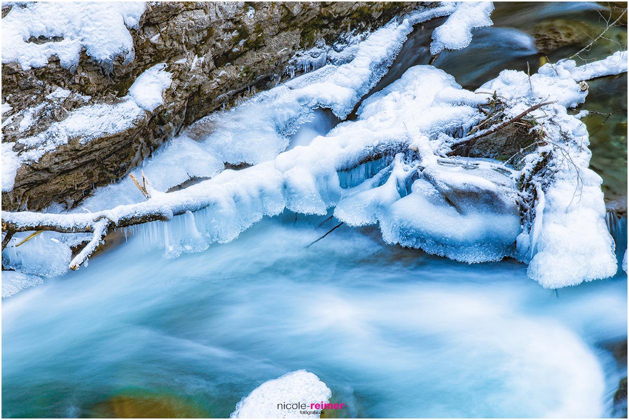 Schneebedeckter Ast und rauschendes Wasser in der Breitachklamm, Deutschland, Nicole Reimer Fotografie